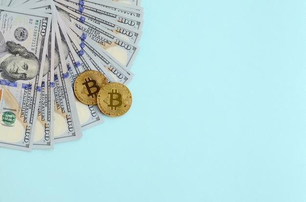 Gouden bitcoins en honderd dollarbiljetten liggen op lichtblauw
