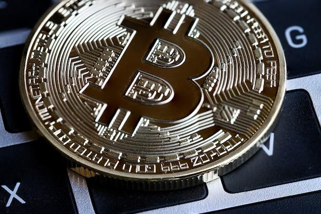 Gouden bitcoins-kring met b-brievensymbool op toetsenbord.