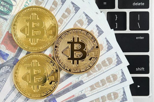 Gouden bitcoins munt en amerikaanse bankbiljetten toetsenbordcomputer. close up van metalen glanzende bitcoin crypto valuta munten en amerikaanse dollar