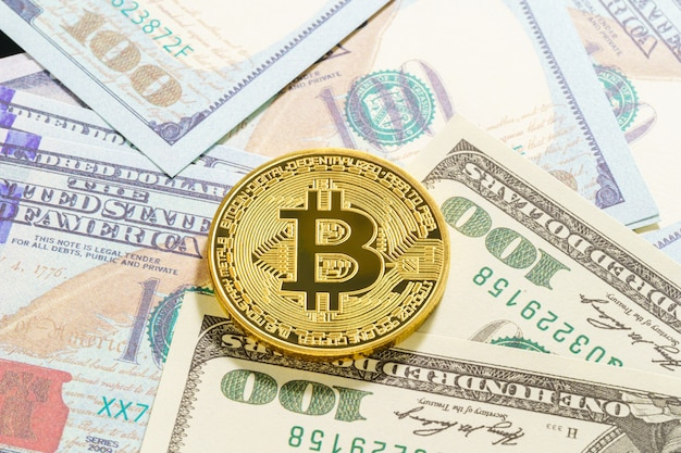 Gouden bitcoins-munt en amerikaanse bankbiljetten van honderd dollar. close-up van metalen glanzende bitcoin crypto-valutamunten en amerikaanse dollar