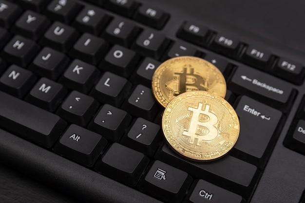 Gouden bitcoins op computertoetsenbord close-up. elektronisch virtueel geld en mijnbouw cryptocurrency concept.