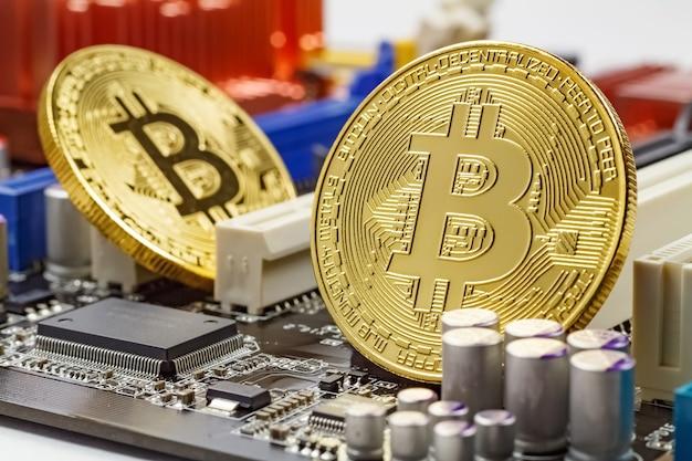 Gouden bitcoins op de computer moederbord achtergrond close-up. virtueel geld met cryptocurrency