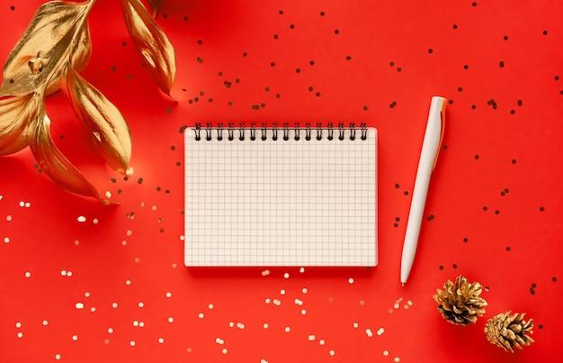 Gouden blad en notitieboekje dat op rood wordt geïsoleerd