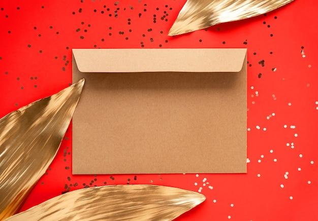 Gouden bladeren en envelop geïsoleerd op rood
