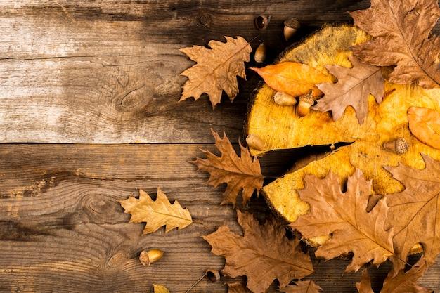Gouden bladeren op houten achtergrondexemplaarruimte