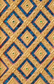 Gouden bloem gesneden op stucwerk van inheemse muur
