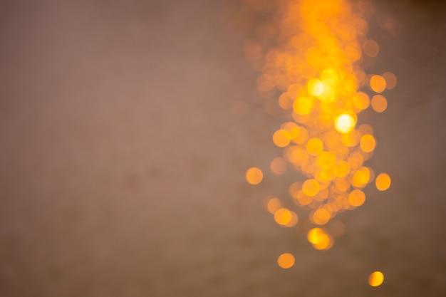 Gouden bokeh veroorzaakt door de weerkaatsing van het licht en het zwembad in de schemering geschikt voor achtergrond