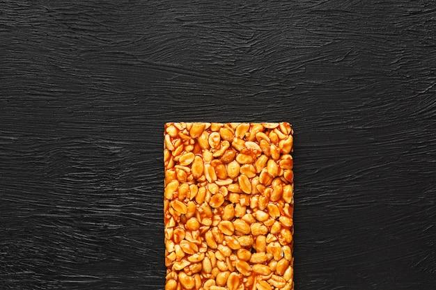 Gouden boletus kozinaki van geroosterde pindabonenergierepen. zwarte textuur achtergrond, bovenaanzicht