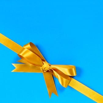 Gouden boog cadeau lint hoek diagonale blauwe achtergrond