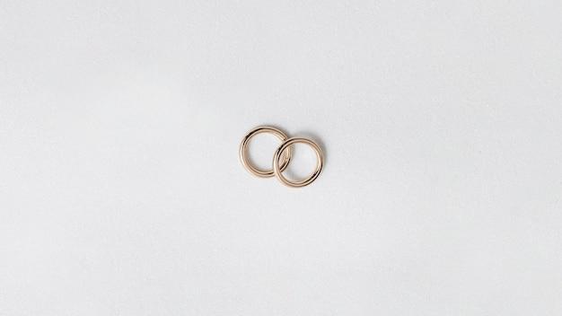 Gouden bruiloftringen die op witte achtergrond worden geïsoleerd