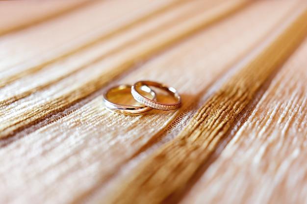 Gouden bruiloftringen met diamanten op beige stoffenachtergrond.