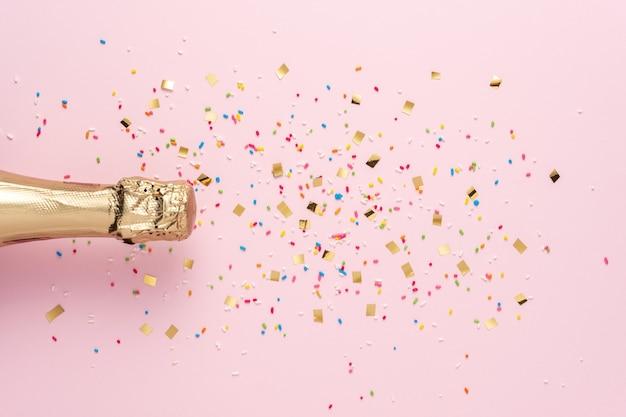 Gouden champagnefles met confetti op roze achtergrond.