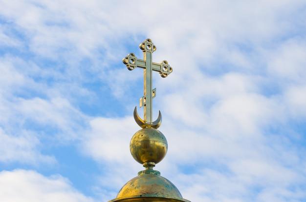 Gouden christelijke kruis op een achtergrond van blauwe lucht.