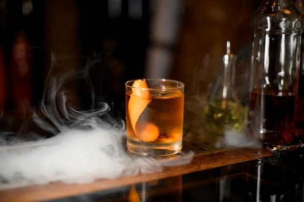 Gouden cocktail in het glas met één ijsblokje en sinaasappelschil in de rook