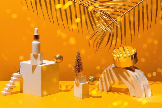 Gouden compositie met crème en serum geometrische vormen en kerstboom