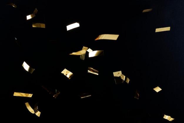 Gouden confettipatroon op een zwart behang