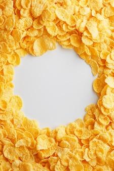 Gouden cornflakes op volledig kader met lege witte ruimte. gezond ontbijt
