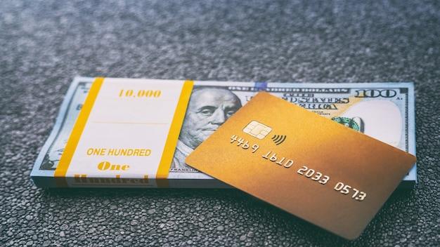 Gouden creditcard ligt op stapel van honderd-dollarbiljetten, close-up