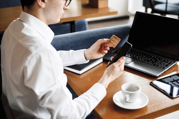 Gouden creditcardhouder door een man in de hand en een smartphone zittend aan een bureau met een laptop erop.