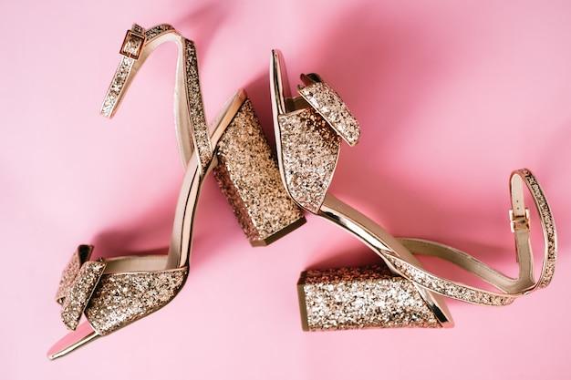 Gouden damesschoenen met hakken en pailletten op roze achtergrond.