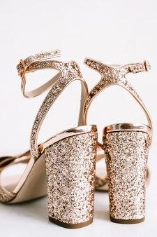Gouden damesschoenen met hakken en pailletten op witte achtergrond.