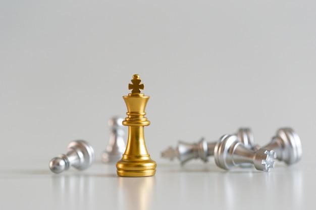 Gouden de koning van het schaakspel status en zilveren achtergrond, bedrijfsstrategieconcept.