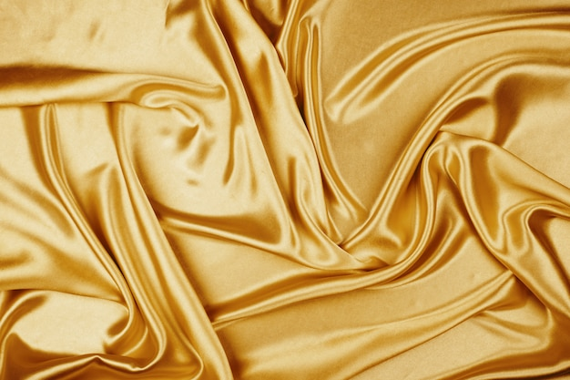 Gouden de stoffentextuur van het luxesatijn voor achtergrond