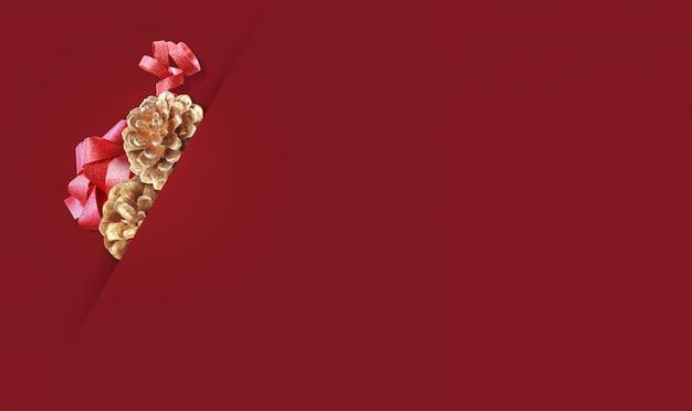 Gouden denneappels op rode achtergrond. vrolijke kerstmis en de gelukkige nieuwe achtergrond van het jaarconcept met exemplaarruimte.