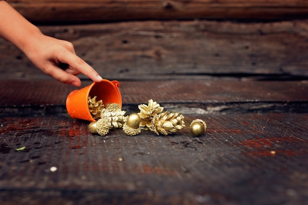 Gouden dennenappels en eikels die uit een kleine oranje emmer stromen