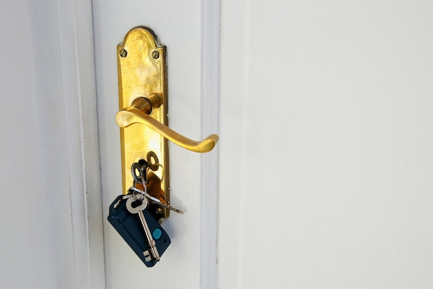 Gouden deurknop met sleutels op een witte deur