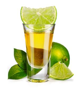 Gouden die tequila met kalk wordt geschoten op wit wordt geïsoleerd