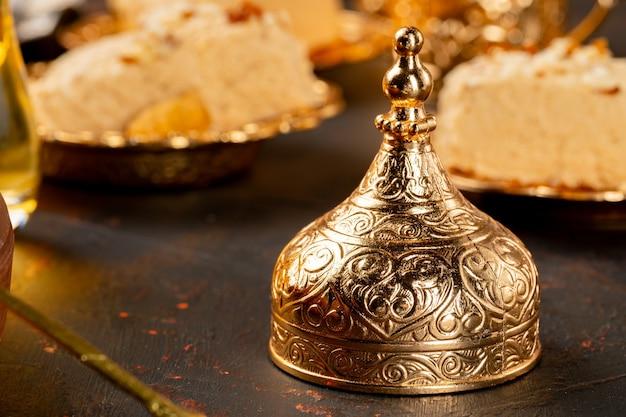 Gouden dop voor turkse beker op donkere ondergrond met halva gebak
