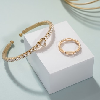 Gouden edelstenen armbanden set met gouden ring op witte kubus display
