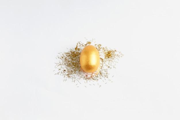 Gouden ei, een symbool van het maken van geld en succesvolle investeringen en gouden schittert op witte achtergrond.