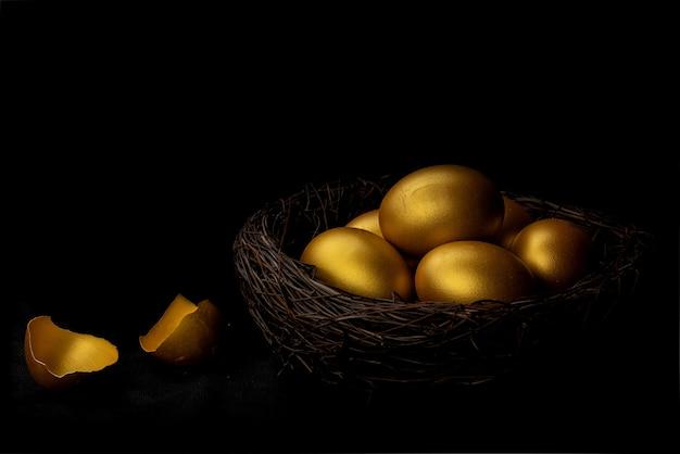 Gouden ei en eierschaal in nest geïsoleerd op zwarte background