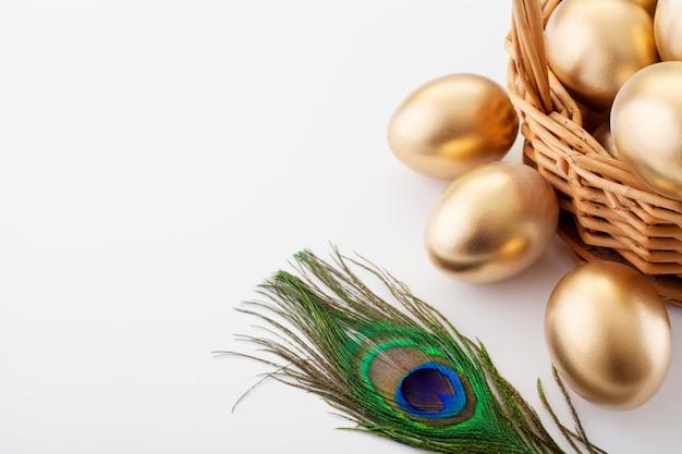 Gouden eieren in een mand, versierd met een pauwenveer.