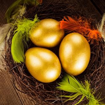 Gouden eieren in het nest over houten achtergrond met exemplaartekst