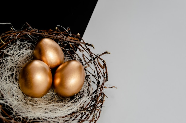 Gouden eieren in nest op zwart-witte abstracte achtergrond.
