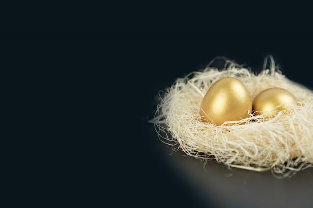 Gouden eieren met stro op zwarte achtergrond.