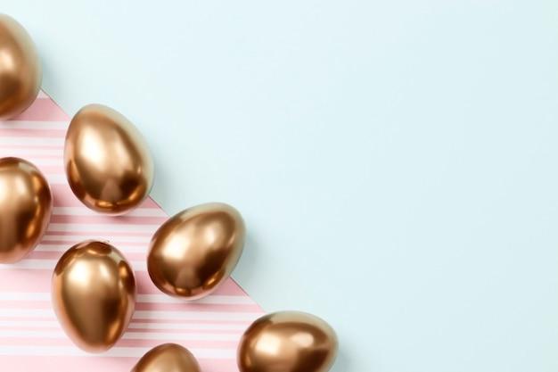 Gouden eieren op blauwe en roze achtergrond