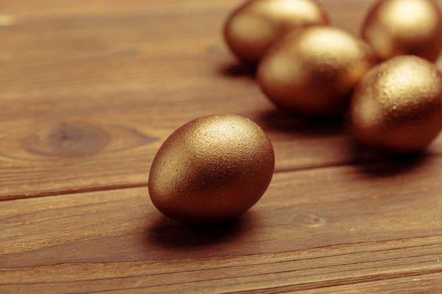 Gouden eieren op houten tafel
