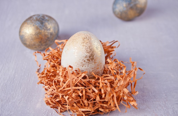 Gouden en kopereieren van pasen in een nest op een grijze achtergrond
