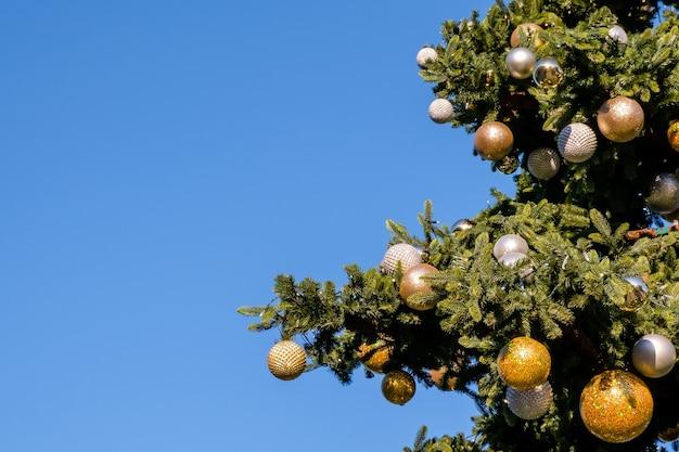 Gouden en witte nieuwjaarsversieringen en slinger op de kerstboom buitenshuis