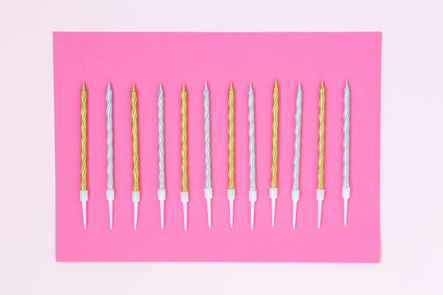 Gouden en zilveren cakekaarsen op een roze achtergrond