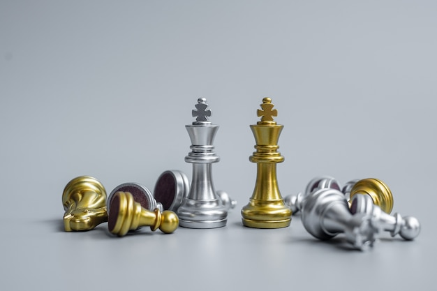 Gouden en zilveren chess king-figuur onderscheiden zich tijdens de schaakbordcompetitie van de menigte van vijanden of tegenstanders.
