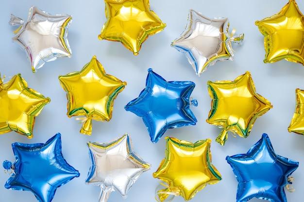 Gouden en zilveren folieballonnen van stervormig op blauwe achtergrond. vakantie en viering concept. verjaardagsdag of feestdecoratie. metalen luchtballonnen. gefeliciteerd. wenskaart.