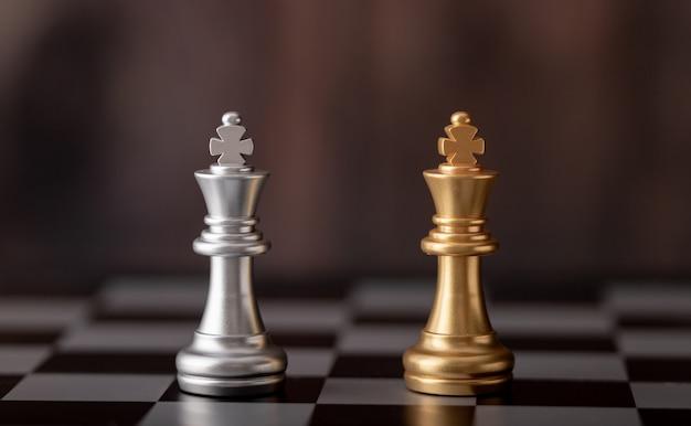 Gouden en zilveren koning staande op schaakbord