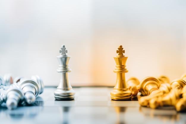 Gouden en zilveren koning van schaakopstelling op stadsachtergrond.