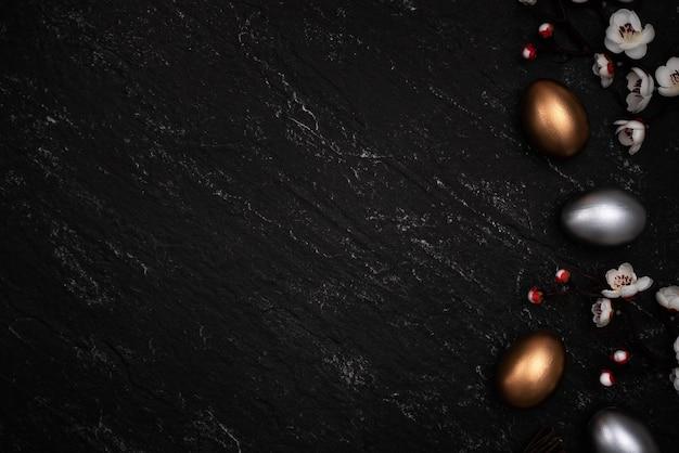 Gouden en zilveren paaseieren met de bloem van de pruimbloesem op donkere zwarte leisteentabelachtergrond.