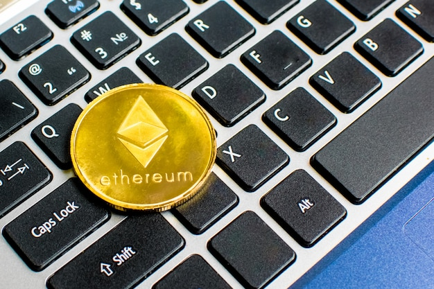 Gouden ethereum-munt met ethereum-symbool op een laptoptoetsenbord naast de enter-toets blockchain.